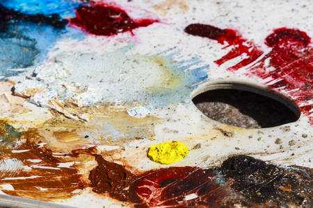 Close-up of an artists oil color palet with various dobs of paint
