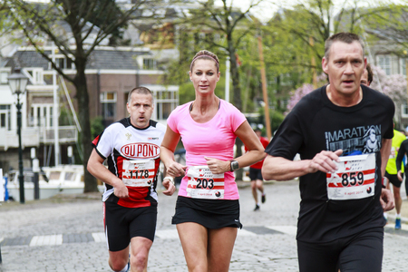 Dordrecht, The Netherlands-April 6, 2014  Competitors running past the harbor in the 67th edition of Dwars door Dordt, a competition run of 5 and 10 km held in the old city center