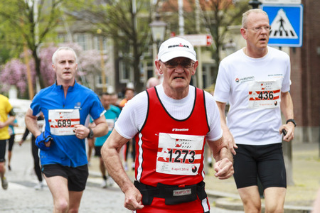 contender: Dordrecht, The Netherlands-April 6, 2014  Older contender dressed in red competing in the 67th edition of Dwars door Dordt, a competition run of 5 and 10 km held in the old city center   Editorial