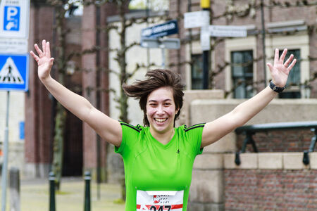Dordrecht, The Netherlands-April 6, 2014  Female runner in green celebrating during the 67th edition of Dwars door Dordt, a competition run of 5 and 10km held in the old city center
