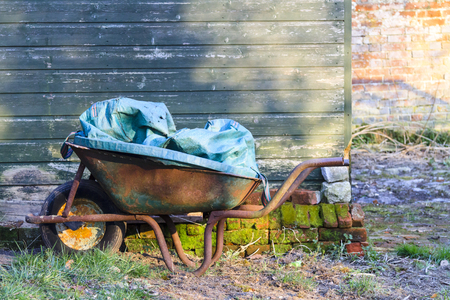 Old rusty wheelbarrow standing in a garden next to a green shed waiting to be used