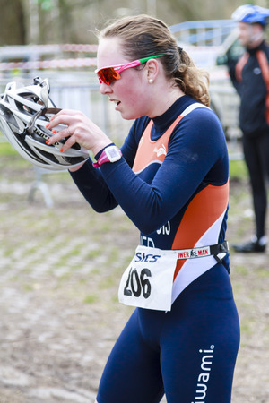 DORDRECHT, NETHERLANDS - APRIL 13 2013  Run Bike Run Bike Run duathlon event organized by TVD  Lindy van Anrooij putting on helmet for the next stage on the course of the dualthlon in Dordrecht