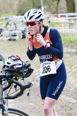 DORDRECHT, NETHERLANDS - APRIL 13 2013  Run Bike Run Bike Run duathlon event organized by TVD  Lindy van Anrooij securing cycling helmet for the next stage on the course of the dualthlon in Dordrecht