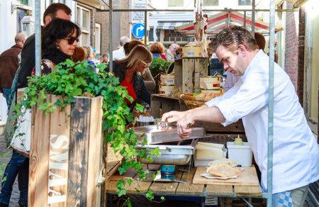 DORDRECHT, NETHERLANDS - SEPTEMBER 29 2013  Customers being served food at a market stall during the event Dordt Pakt Uit in the old city center of Dordrecht