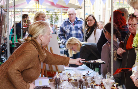 DORDRECHT, NETHERLANDS - SEPTEMBER 29 2013  Stall holder offering samples of chocolate to customers at a market stall during the event Dordt Pakt Uit in the old city center of Dordrecht