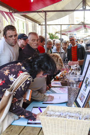 DORDRECHT, NETHERLANDS - SEPTEMBER 29 2013  Curious shoppers look on as people enter into competion to win prizes at a market stall during the event Dordt Pakt Uit in the old city center of Dordrecht