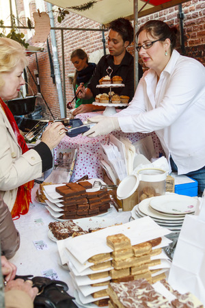 DORDRECHT, NETHERLANDS - SEPTEMBER 29 2013  Customer paying with credit card for products on stall selling tea cakes and chocolate during the event Dordt Pakt Uit in the old city center of Dordrecht  Redakční