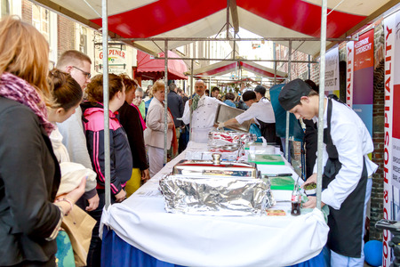 DORDRECHT, NETHERLANDS - SEPTEMBER 29 2013  Customers watching as cooks set up food stall at a farmers market during the event Dordt Pakt Uit in the old city center of Dordrecht