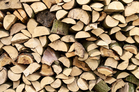 Background of firewood Logs stacked up on top of each other to form a wall Stock Photo