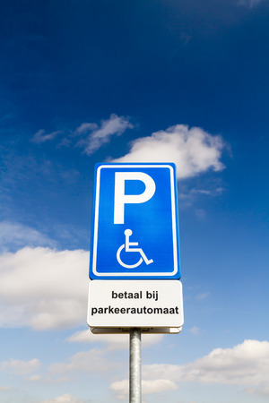 Blue handicapped parking sign for disabled drivers against a dramatic sky Фото со стока