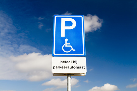 Blue handicapped parking sign for disabled drivers against a dramatic sky photo