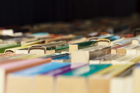 Colorful old books lined up for sale in a flea market