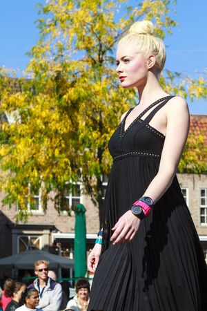 DORDRECHT, NETHERLANDS – SEPTEMBER 29 2013  Free entertainment and fashion show in the main square organized by the municipality  Beautiful blond model walks on the catwalk showcasing a black dress