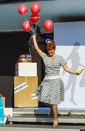 DORDRECHT, NETHERLANDS – SEPTEMBER 29 2013: Free entertainment and fashion show in the main square organized by the municipality. Mature model holding red balloons on podium entertaining the crowd.