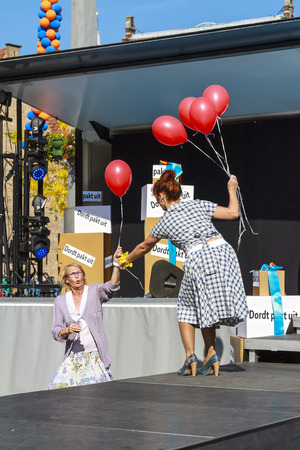 DORDRECHT, NETHERLANDS - SEPTEMBER 29 2013: Free entertainment and fashion show in the main square organized by the municipality. Mature model with red balloons on podium entertaining the crowd.