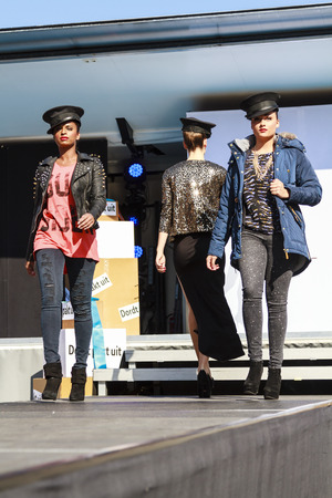 DORDRECHT, NETHERLANDS - SEPTEMBER 29 2013: Free entertainment and fashion show in the main square organized by the municipality. Three models on the catwalk showcasing the new autumn collection.