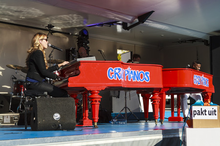 DORDRECHT, NETHERLANDS - SEPTEMBER 29 2013: Free entertainment and music on stage in the main square organized by the municipality. Jennifer Lynn playing duo with Crazy Pianos pianist Stevie J. Redakční