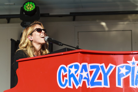 DORDRECHT, NETHERLANDS - SEPTEMBER 29 2013: Free entertainment and music on stage in the main square organized by the municipality. Jennifer Lynn, Crazy Pianos pianist playing and singing on stage.