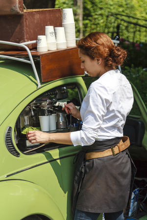 DORDRECHT, NETHERLANDS - AUGUSTUS 10, 2014: Young girl operating coffee machine out of a car at the Swan Market in Dordrecht. The lifestyle market was originally started in vacant shops in Rotterdam