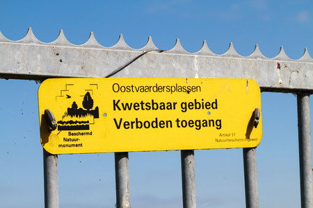 ALMERE, NETHERLANDS - SEPTEMBER 1, 2014: Yellow warning sign sensitive area and forbidden access, attached to a spiked iron fence. Oostvaardersplassen is a vast nature reserve with lakes and grassland Editorial