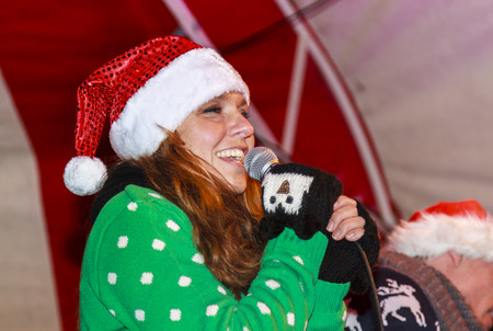 dordrecht: DORDRECHT, NETHERLANDS - DECEMBER 13, 2013: Female singer wearing a Santa hat at the Christmas Market in Dordrecht. The market is the largest and busiest X-mas market in Holland. Editorial