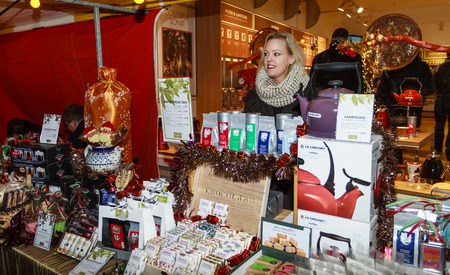DORDRECHT, NETHERLANDS - DECEMBER 13, 2013: Stallholder standing in the cold selling products at the Christmas Market in Dordrecht. The market is the largest and busiest X-mas market in Holland.