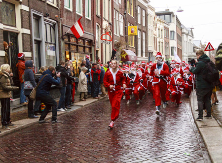 DORDRECHT, NETHERLANDS - DECEMBER 21, 2013: Unidentified Santa\'s starting the run in the old streets of Dordrecht. The Santa run is organized every year to raise money for Dordrecht Editorial