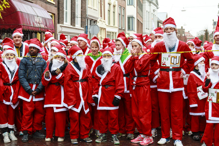 DORDRECHT, NETHERLANDS - DECEMBER 21, 2013: Unidentified Santa\'s assembling at the start line for the run in Dordrecht. The Santa run is organized every year to raise money for Dordrecht Rotary Club Editorial