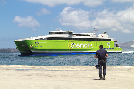 dockside: SANTORINI, GREECE - MAY 30, 2014: Green and white highspeed ferry arriving at the port of Santorini on a sunny day while a port of authority policeman waits at the dockside.