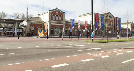 dordrecht: DORDRECHT, THE NETHERLANDS – APRIL 17, 2015: Dordrecht central train station is decorated with flags in preparation of the king and queens visit to celebrate kings day which is an annual holiday.