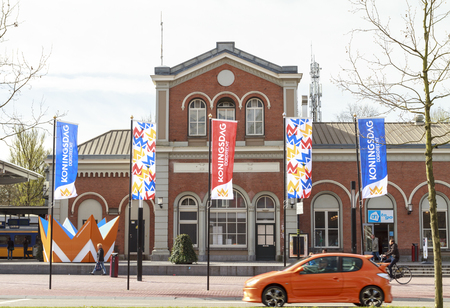 DORDRECHT, THE NETHERLANDS – APRIL 17, 2015: Orange car passing and display of flags in front of Dordrecht central train station in preparation of the king and queens visit.