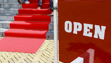 Red and white sign with the word open welcoming visitors as they climb the steps to enter the building