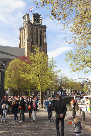 dordrecht: DORDRECHT, THE NETHERLANDS - APRIL 27, 2015: Crowds gather by Dordrecht cathedral awaiting the visit of the Dutch royal family during the traditional Kings Day celebrations.