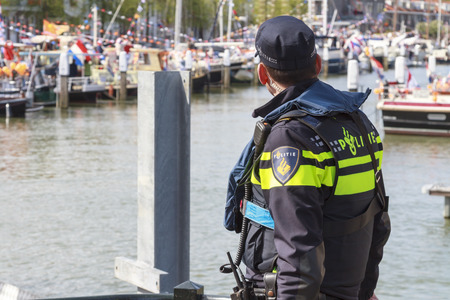 DORDRECHT, THE NETHERLANDS - APRIL 27, 2015: Police officer keeping watch in Dordrecht during the visit of the Dutch royal family during the traditional Kings Day celebrations.