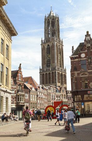 UTRECHT THE NETHERLANDS MAY 11 2015: People shopping on the streets in the city center of Utrecht with the historical Dom cathedral in the background.
