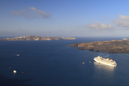 Santorini Greece May 30 2014: Early morning activity around cruise ship anchored in the blue seas of the Bay of Fira on Santorini in beautiful sunlight.