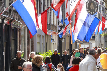 DORDRECHT, THE NETHERLANDS - APRIL 27, 2015: Visitors shopping on Vleeshouwersstraat street full with flags during the visit of the Dutch royal family on the traditional Kings Day celebrations.