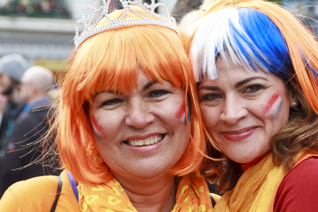 dordrecht: DORDRECHT, THE NETHERLANDS - APRIL 27, 2015: Women dressed in orange wearing wigs with painted faces on Hollands national Kings day celebrations in the old center of Dordrecht.