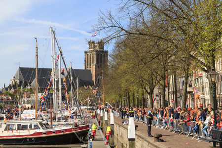 dordrecht: DORDRECHT, THE NETHERLANDS - APRIL 27, 2015: Crowds gather by the harbor in Dordrecht awaiting the visit of the Dutch royal family during the traditional Kings Day celebrations. Editorial