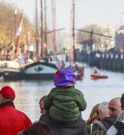saint nicolas: DORDRECHT, THE NETHERLANDS - NOVEMBER 12, 2011: Child wearing a puple hat sitting on shoulders waiting for the arrival of the boat of Saint Nicolas in the historical harbor of Dordrecht