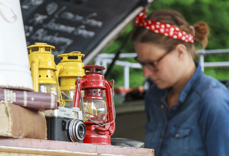 red oil lamp: DORDRECHT, NETHERLANDS - July 26, 2015: Retro artifacts decorating an old timer converted bus at the Swan Market in Dordrecht. A woman prepares drinks in the background. The lifestyle market is extremely popular in the summer months