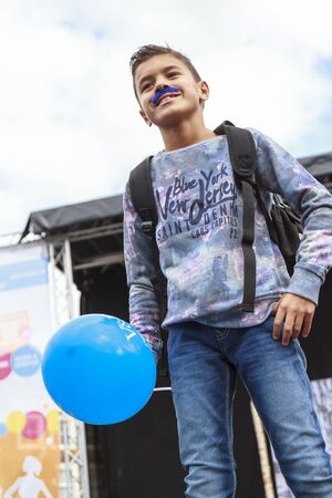 DORDRECHT, NETHERLANDS - SEPTEMBER 27 2015: Free fashion show in the main square organized by the municipality. Child model holding a blue balloon on the catwalk showcasing the new autumn collection.