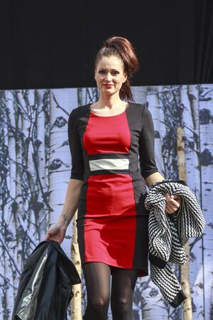 DORDRECHT, NETHERLANDS - SEPTEMBER 27 2015: Free entertainment fashion show in the main square organized by the municipality. Model in red outfit on the catwalk showcasing the new winter collection. Editorial