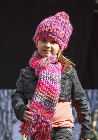 DORDRECHT, NETHERLANDS - SEPTEMBER 27 2015: Free fashion show in the main square organized by the municipality. Child model dressed in pink on the catwalk showcasing the new autumn collection.
