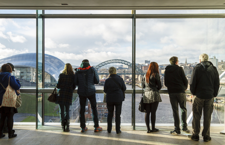 NEWCASTLE, ENGLAND - DECEMBER 7 2014: People looking out the window of the Baltic at the city view of Newcastle upon Tyne. Editorial