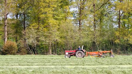 LEUSDEN NETHERLANDS - MAY 6 2016: Farmer on the tractor pulling grass mower cutter through a lush green field. Editorial