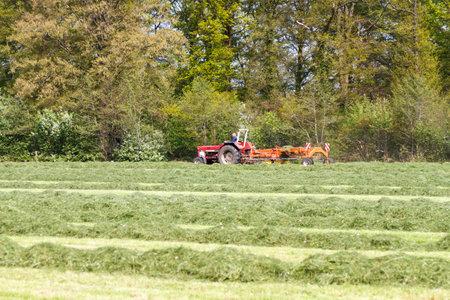 LEUSDEN NETHERLANDS - MAY 6 2016: Farmer driving a red tractor pulling grass mower cutter through a lush green field.