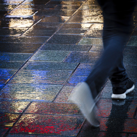 waist down: Person walking in the reflection of neon lights on the wet sidewalk. Stock Photo