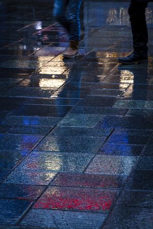 waist down: People walking in the reflection of neon lights on the wet sidewalk in the dark.