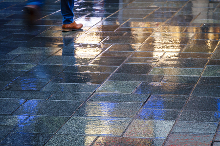 waist down: Brown shoes walking in the reflection of neon lights on the wet sidewalk.